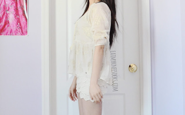 A cute spring/summer outfit featuring a sheer golden Abercrombie blouse, worn with beige cream off-white layered tiered crochet lace shorts from Wholesalebuying.