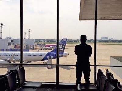 foto orang berdiri di depan kaca sambil melihat pesawat yang baru landing