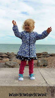 Toddler on the wall at the beach wearing her new shoes