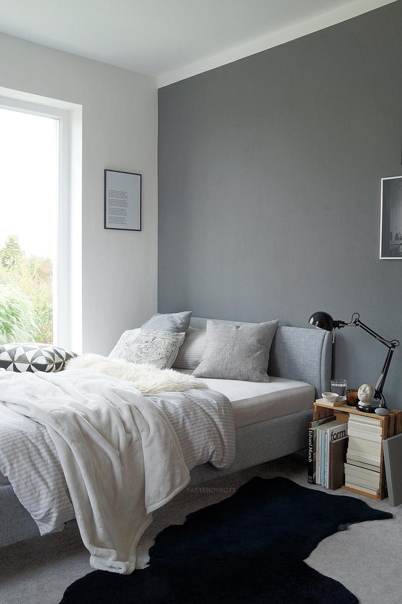 Schlafzimmer im Herbst einrichten und dekorieren in Grautönen und Weiß, mit vielen Wohntextilien für eine gemütliche Atmosphäre, Deko mit Fellen, Kissen, Decken; graues Bett mit Kopfteil, weiße und dunkelgraue Wände, Weinkiste mit Büchern als Nachttisch