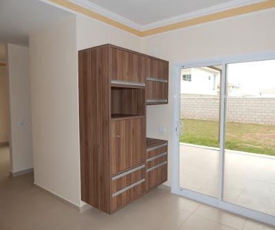 A cozinha conta com marcenaria completa, com gaveteiros e nichos para fornos de microondas e elétrico. Na esquerda fica o acesso para a sala de jantar, que também se comunica com a varanda gourmet à direita.