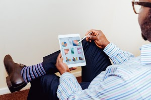 Business man analyzing graphs on a tablet  Business man analyzing graphs on a tablet