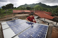 A woman inspects solar panels in the rural village of Tinginaput, India. (Credit: Abbie Trayler-Smith (Dfid)/Flickr) Click to Enlarge.