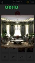 Овальное помещение в котором несколько больших окон и люстра на верху. стоит мягкая мебель и ковер на полу