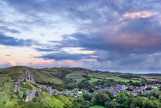 National Trust ruins of Corfe Castle under stormy sunset clouds