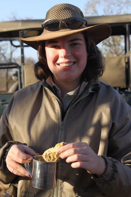 A ranger dipping her rusk in her billy can of rooibos tea. Kruger Park.