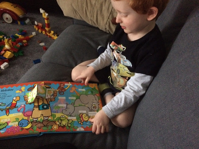 A 3 year old child sitting on a sofa reading a book