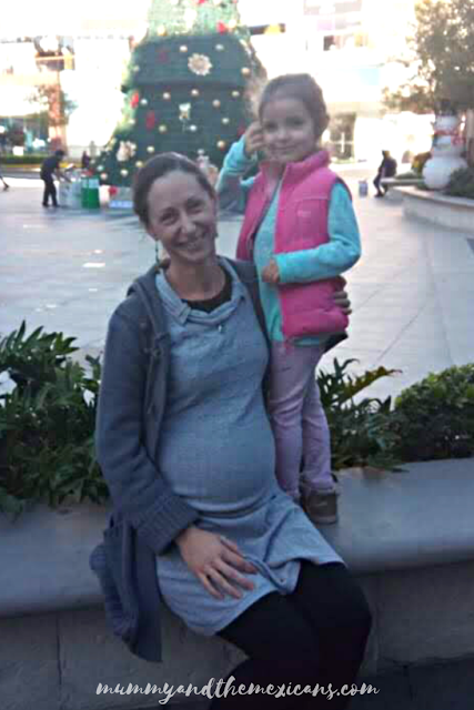 Pregnant Woman Sitting On A Wall In An Outdoor Shopping Mall With Christmas Tree In The Background And Little Girl Standing Next To Her On The Wall