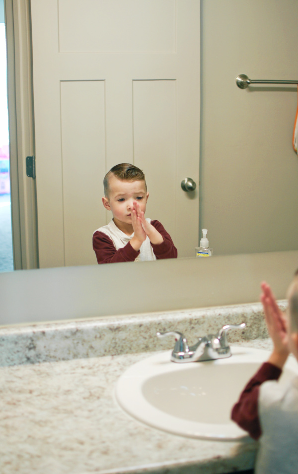Little boy washes hands after potty training.