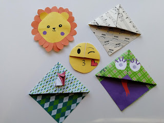 Andrea's bookmarks. All corner bookmarks - one lion. one forest with a rubbish origami fox, one green monster with big eyes and a tongue, one kissy face emoji and one made from old music manuscript