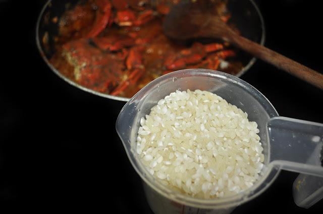 una jarra con arroz, al fondo la sartén con las nécoras