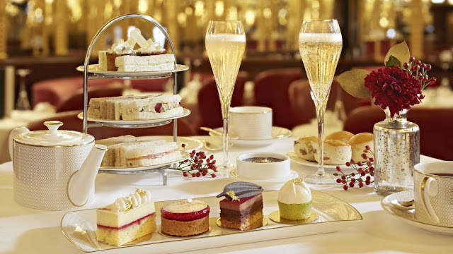 a table set for high tea with sandwiches, sweets, and champagne