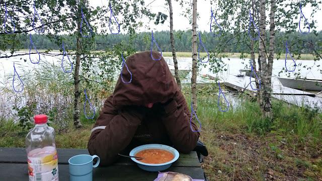 Henkilö istuu huppu päässä ruokapöydässä ulkona