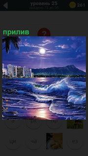 Вдали стоит отель и волны накатываю на берег, происходит прилив