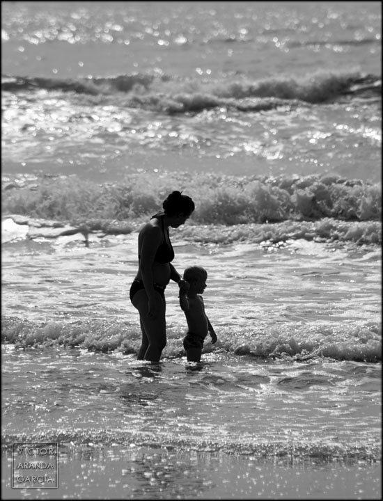 Fotografía a contraluz de una madre y su hijo en el mar con olas de fondo