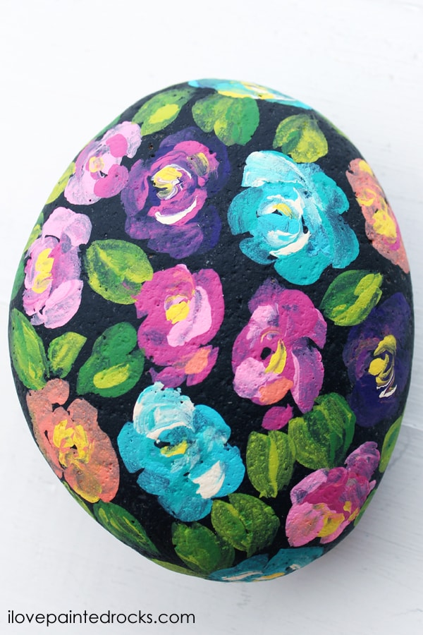 Bright colored loose florals painted on a black rock perfect tutorial for beginners.