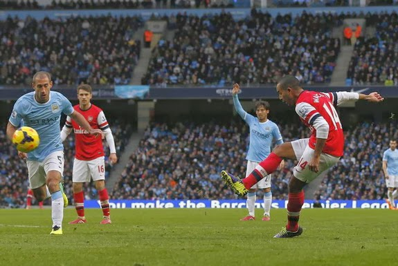 Arsenal forward Theo Walcott shoots to score his second goal against Manchester City