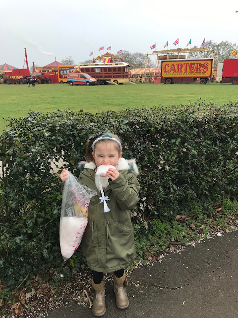My niece eating candy floss, saying goodbye to Carters Steam Fair, wearing her hook a duck prize on her head.