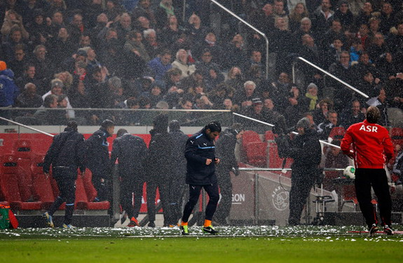 Part of the Amsterdam ArenA roof gives way and snow falls on the bench