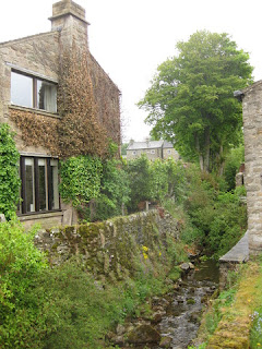 Stream flowing over a rocky bed between stone walls and homes, Yorkshire Dales, England