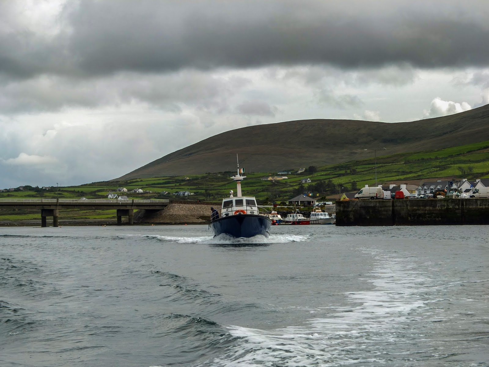 A blue and white boat leaving Portmagee Harbour in Co.Kerry.