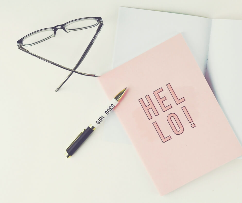 A girl boss pen laying on top of a pink notebook that says Hello on the front of it.