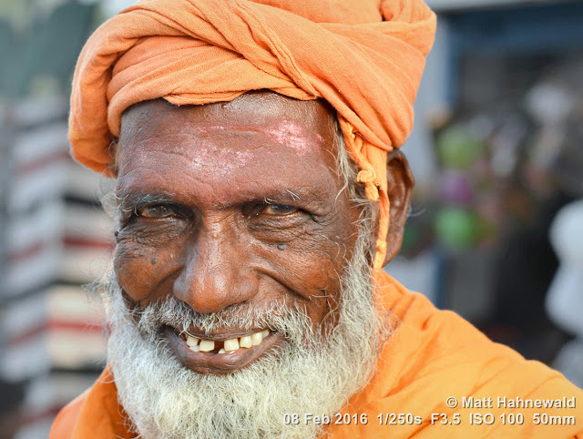 Matt Hahnewald Photography; Facing the World; closeup; street portrait; headshot; outdoor; Asia; South Asia; India; Tamil Nadu; Tiruchirappalli; Srirangam; Ammamandapam; ghats; Nikon D3100; Nikkor AF-S 50mm f/1.8G; travel; travel destination; beggar; photography; colour; portraiture; person; people; eyes; eye contact; Indian man; face; white beard; poor; horizontal; ethnic; modern India; orange turban; orange robe