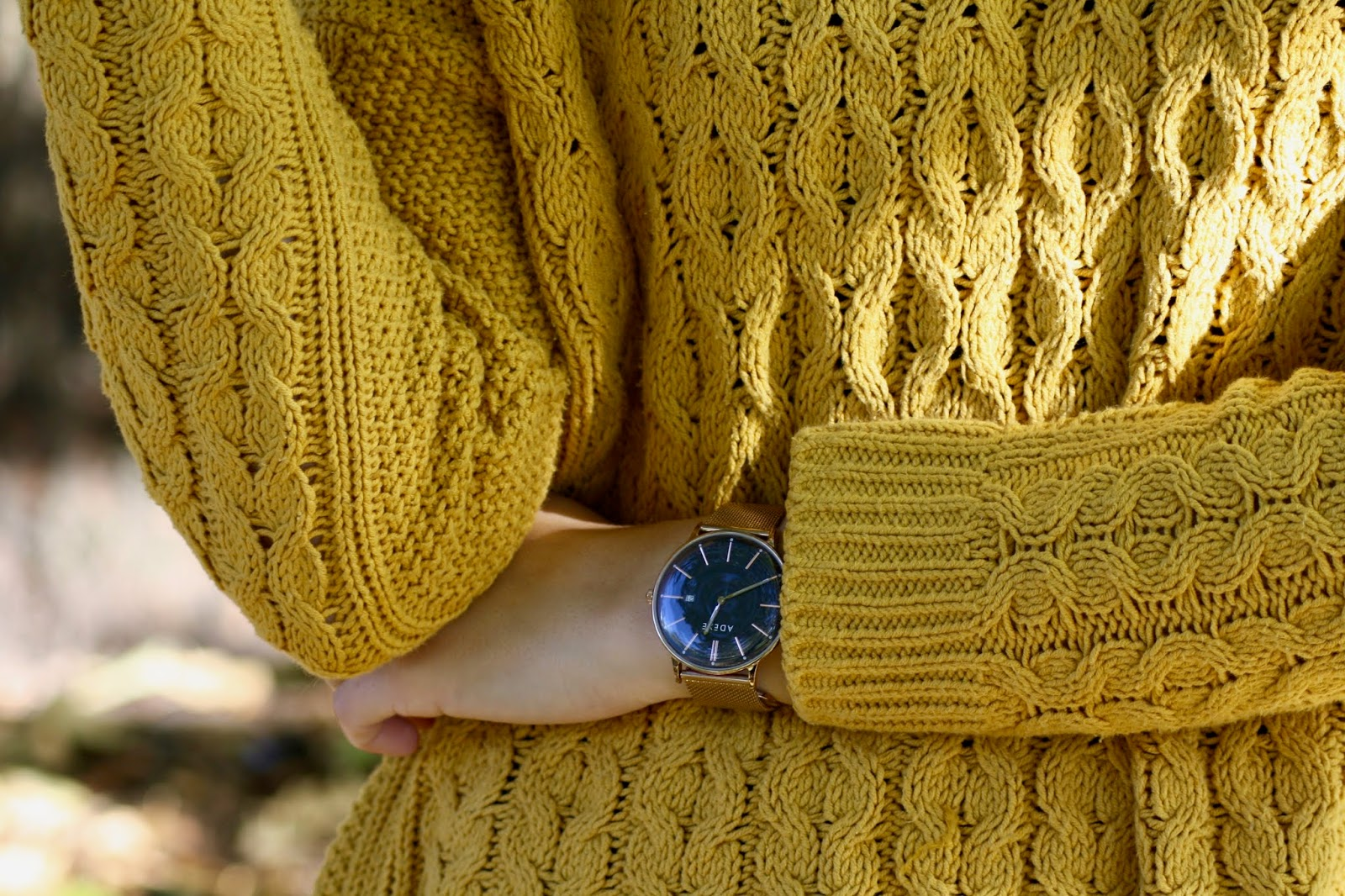 a close up of abbey's torso, wearing a mustard knit jumper, showing a gold watch on her wrist