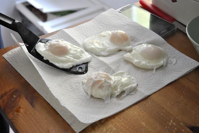 Eggs Benedict zum Abtropfen auf ein Küchentuch legen