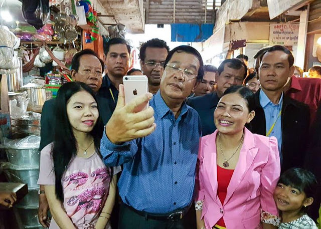 Prime Minister Hun Sen takes a photo with local residents at a market in Kampong Thom province on Saturday during a tour of the Kingdom's provinces. Facebook