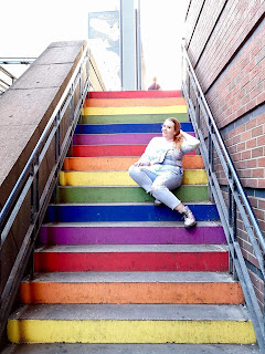 A long shot of Michelle with a blonde ponytail wearing a beige jumper, light blue pants and sparkly silver Doc Martens spread out on a rainbow staircase