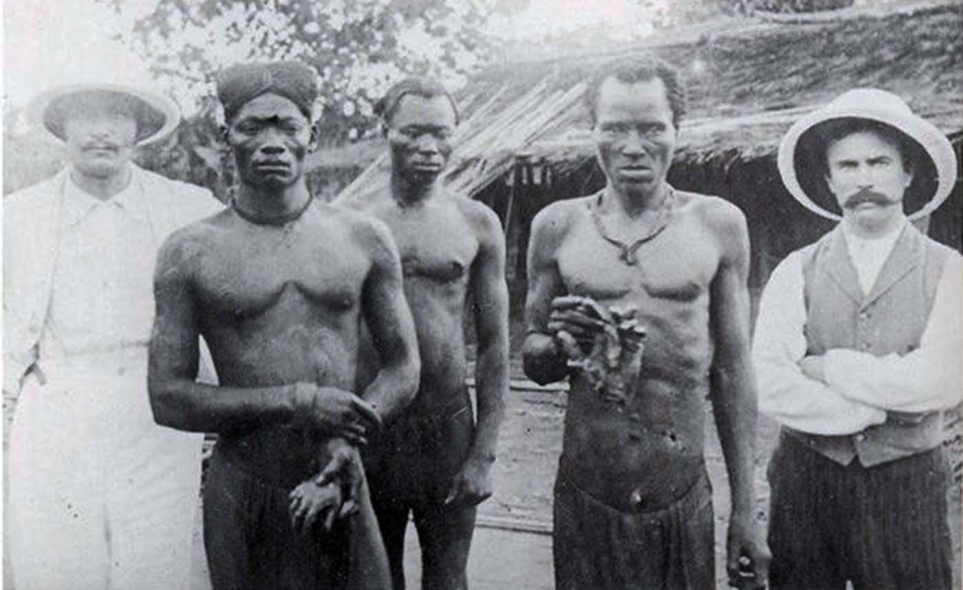 British missionaries with men holding hands severed from victims Bolenge  and Lingomo by ABIR militiamen, 1904.