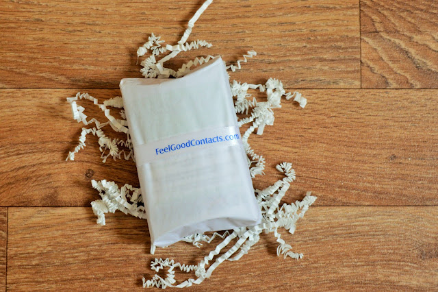 Brown flooring with white package on top of white shredded paper.