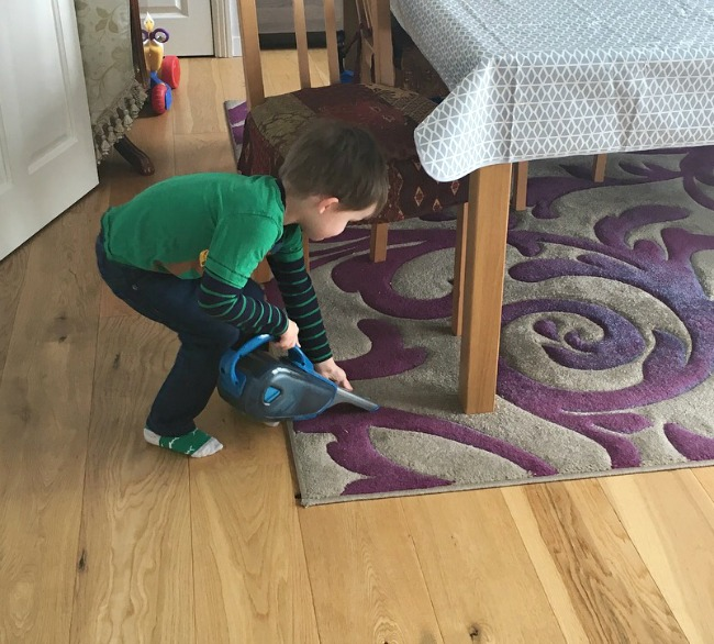 boy-cleaning-floor-with-hand-held-cordless-vacuum
