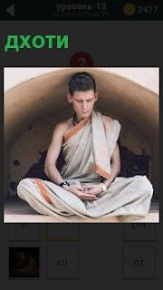 На полу сидит парень в национальной одежде дхоти, медитируя сложив руки перед собой