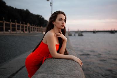 Chica vestida de rojo apoyada en un muro mirando al mar