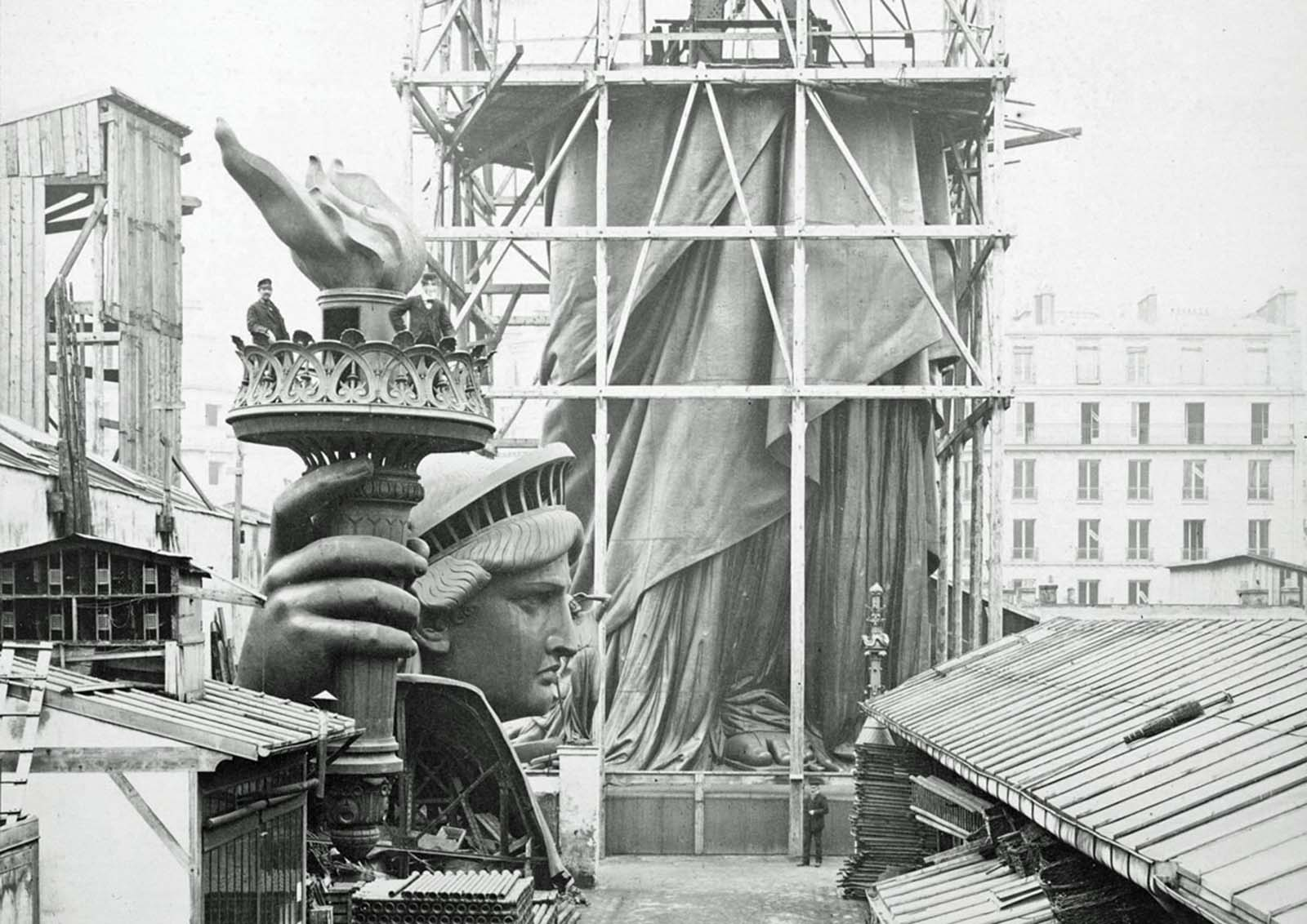 Assemblage of the Statue of Liberty in Paris, showing the bottom half of the statue under scaffolding, with the head and torch at its feet, photographed in 1883.
