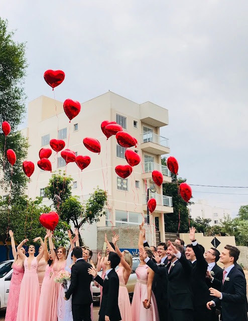 https://www.pexels.com/photo/women-wearing-pink-dresses-and-men-wearing-black-suit-jacket-and-pants-raising-hands-with-red-heart-balloons-673659/