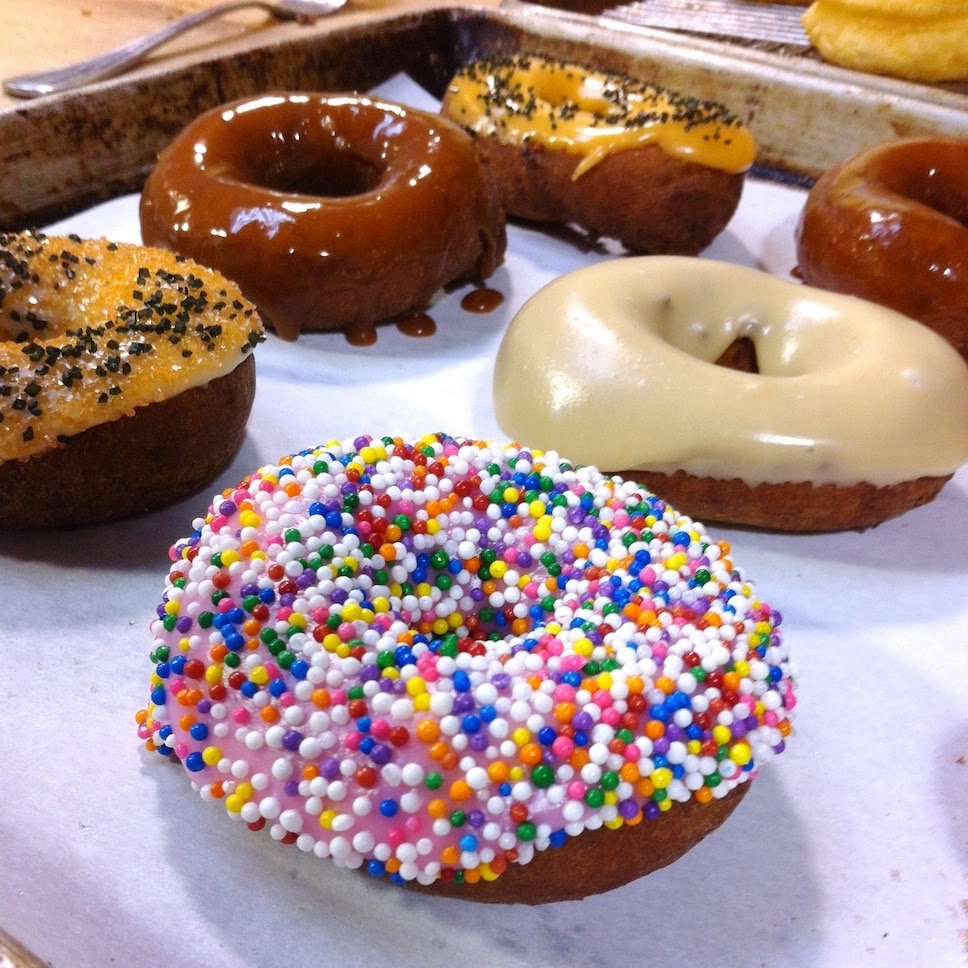 A close up of a doughnut covered with different toppings sitting on a table