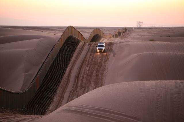 रेत के टीलो के साथ खिसकती है मैक्सिको सीमा  की दीवार।