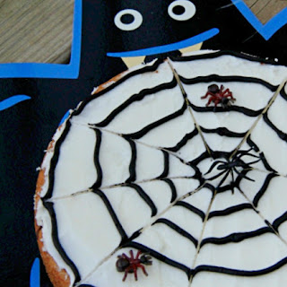 cookie decorated like a spider web with fake spiders on it