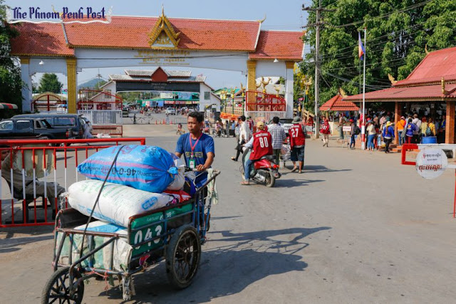 A porter pushes goods across the Thai-Cambodian border in Battambang in April. Heng Chivoan