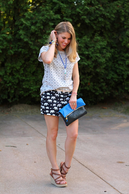 grey eyelet top, elephant print shorts, wedges, blue clare v. clutch