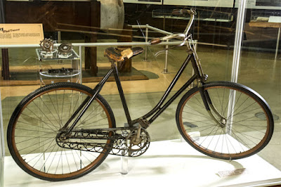 Wright Brothers bicycle in glass case in museum.