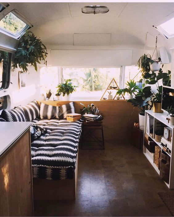 day bed with black and white stripe pattern on a plant-filled airstream