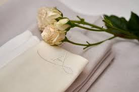 A wilting white rose next to an embroidered handkerchief