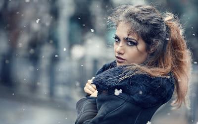 Linda chica en la nieve con chaqueta mirando a cámara