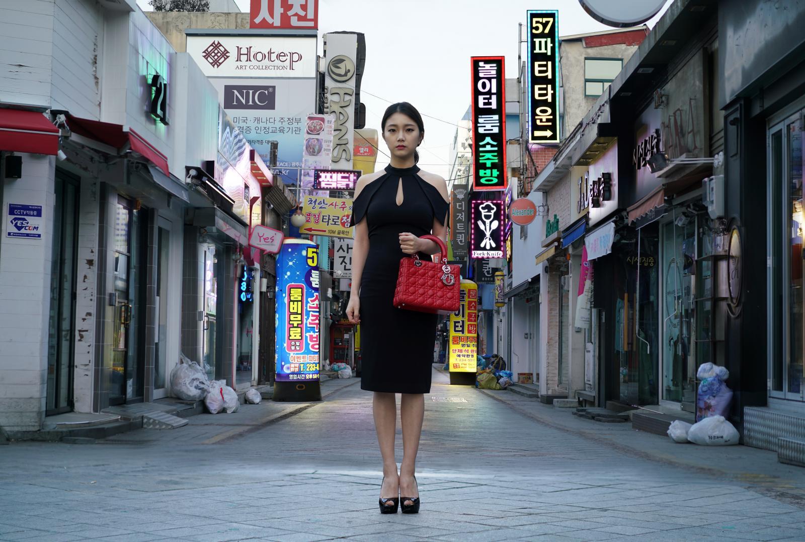 Chica coreana con un bolso de Dior en una calle de prostitución encubierta