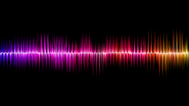 Colourful sound wave on black background, in purple, pink, orange, and yellow