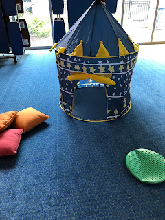 blue pop-up tent with yellow stars on carpeted floor next to 3 orange and pink pillows to the left and a green cushion to the right